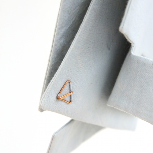 Close up detail of blue linen fabric piece with copped triangle detail.