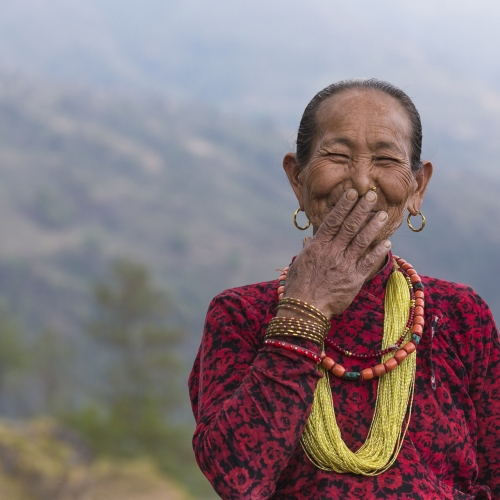 Asian woman laughing and holding hand to mouth.