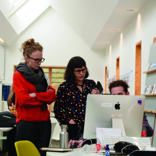 Two women standing looking at an iMac