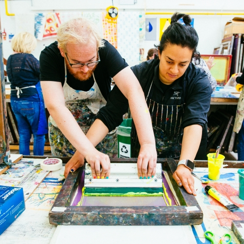 Two people screenprinting in a workshop