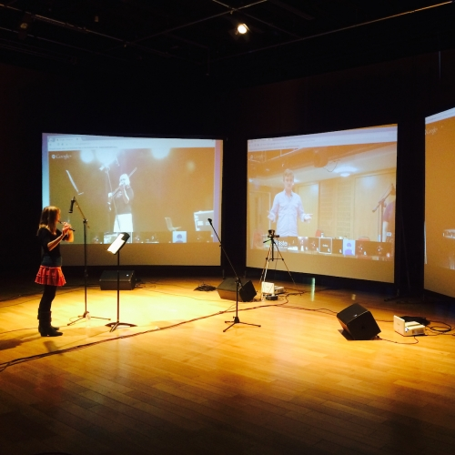 A woman playing the flute in front of three screens