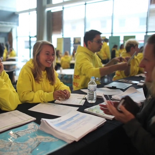 Falmouth ambassadors in their yellow sweatshirts talking to guests at Open day.