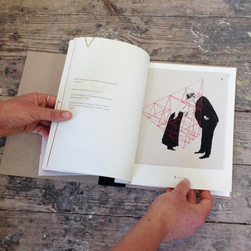 Hand opening book with illustration of victorian couple kissing inside a red prism structure.