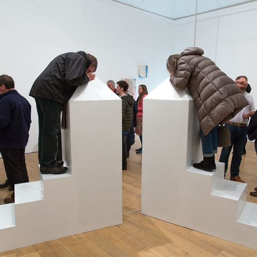 Gallery space filled with people talking and 2 people peering into a white box at the top of steps.