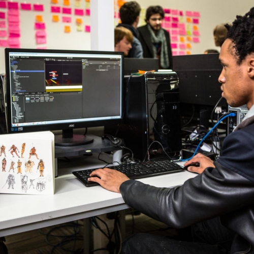 Games student working at computer, sketch book open to show hand drawn character designs.