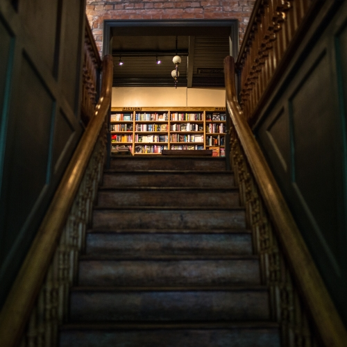 View up a staircase to shelves filled with books.