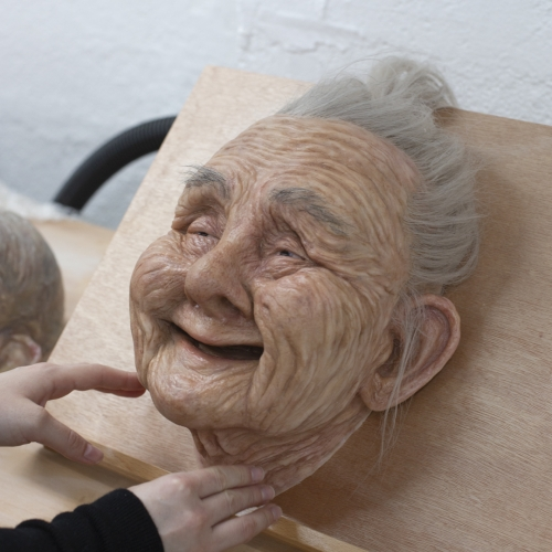A sculpted head of an old woman with grey hair