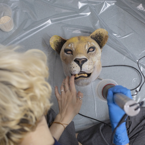 A student working on a model of a lion's head