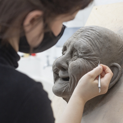 A student creating a clay model of an old woman