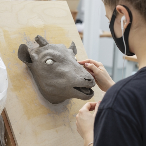 A student working on a clay model of a goat's head