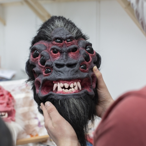 A model of a gorilla's head with multiple eyes