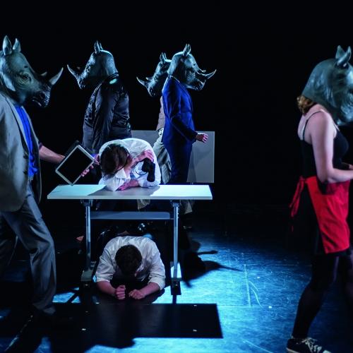 Actors wearing rhinoceros masks on stage.