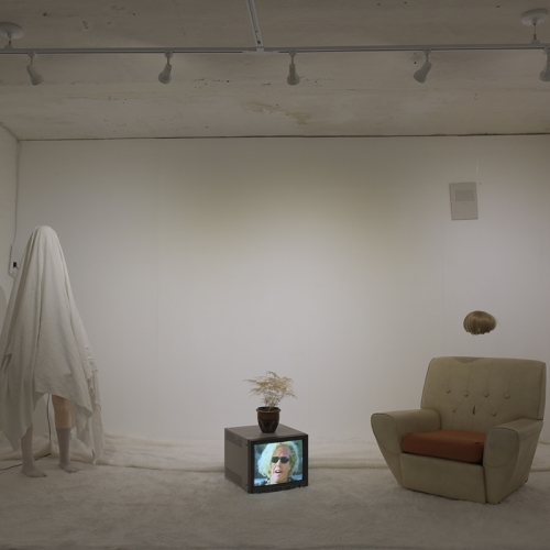 Room installation art, figure covered by white sheet, television on floor with woman's face, armchair, fan, wig suspended in the air.