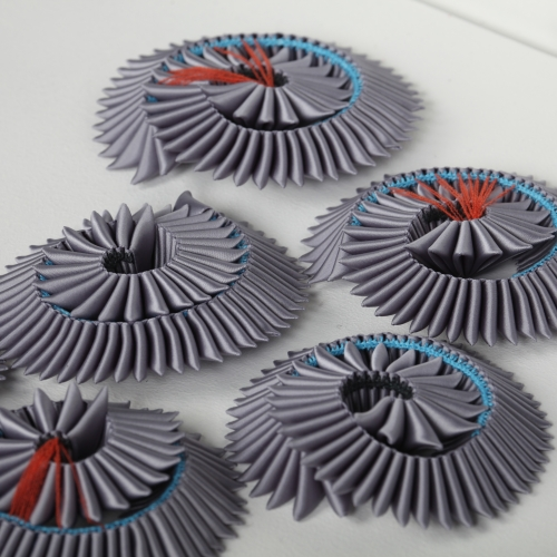 Grey fabric pleated and manipulated into spiral shape.