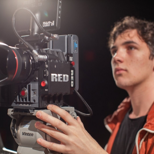 Close up of student holding film camera.