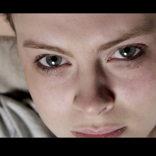 Film still of female staring into camera, makeup smudged.