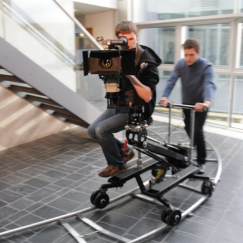 Student behind camera on camera dolly being moved along a track.