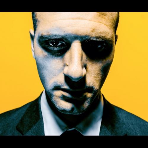 Film still headshot, man in suit, yellow background.