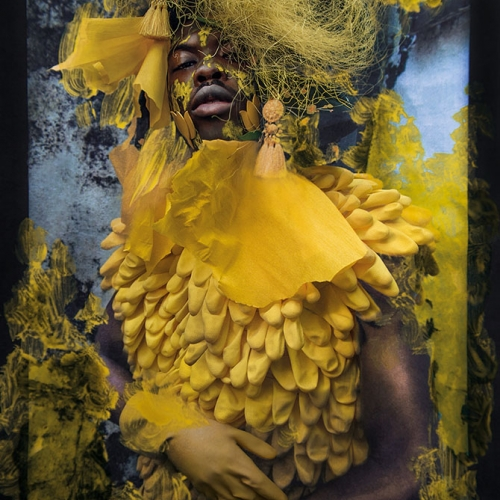 Model with yellow paint on face wears a variety of yellow fabrics of different textures and looks to camera. Head and torso crop.