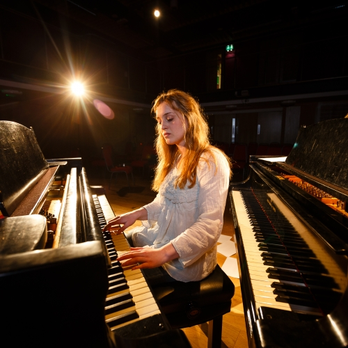 Female student sat between two pianos and playing one of them, sheet music on floor.