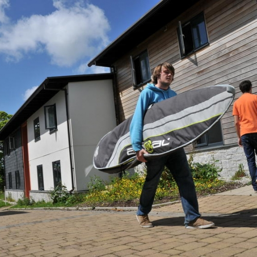 Student carrying surfboard outside student accommodation.