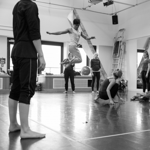 Student dancer jumping high and twisting dance studio as others look on.