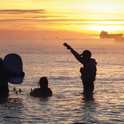 Film students waist deep in sea filming rubber ducks.