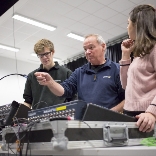 Falmouth University technician showing two people how to use recording equipment