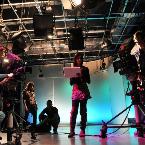 Students with cameras in television studio.