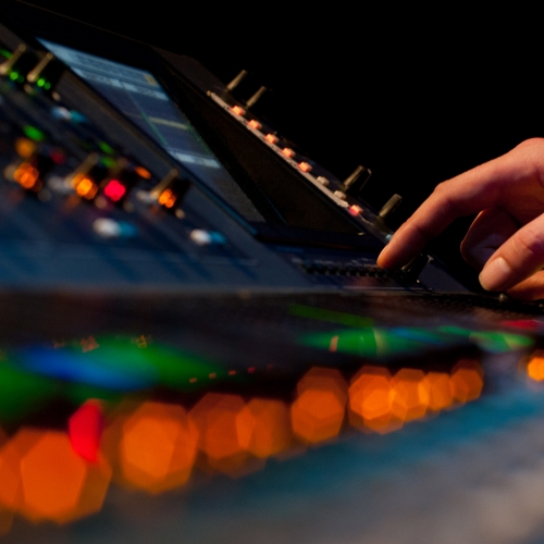 Close up of lights and buttons on mixing desk.