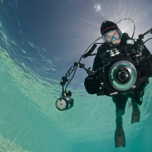 Student in diving gear with camera pointing at the photography, circle of blue water above him.