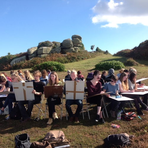 Group of students sitting on chairs in circle, facing outwards and drawing the landscape of Tresco, Isles of Scilly