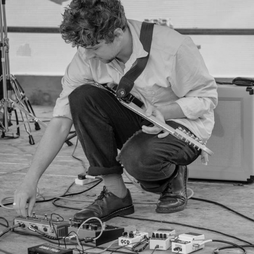 Guitarist on stage bending down and making adjustments to devices on the floor.
