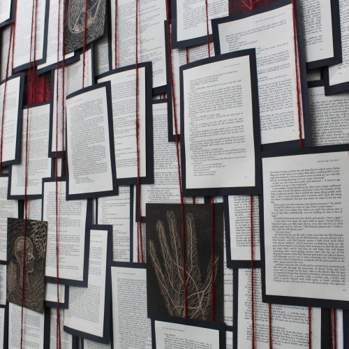 Many pages of black mounted text and images hanging on red strings.