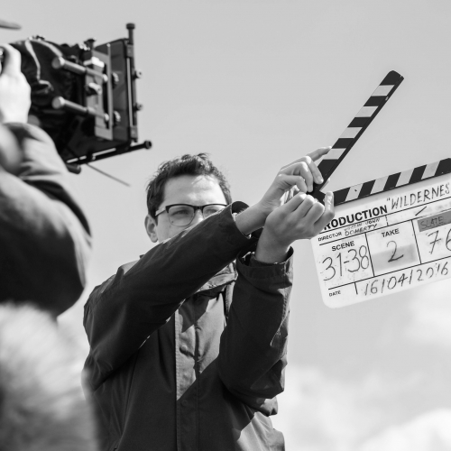 Grayscale image of student with clapperboard in front of camera.