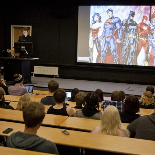 Dr Will Brooker talks with Film students, slide of Marvel characters in background.