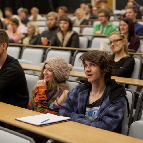 Students listening and smiling in lecture theatre.