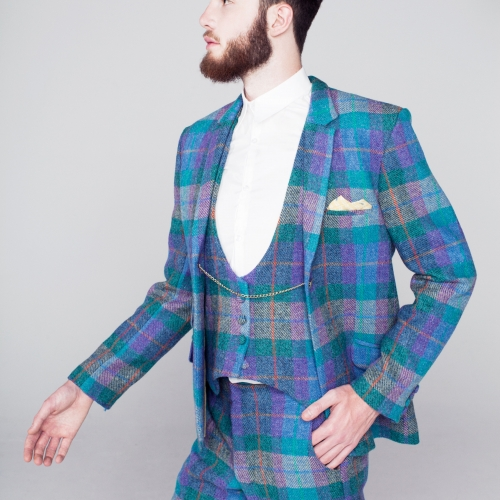 Male model in bright blue and purple tartan 3 piece suit with white shirt.