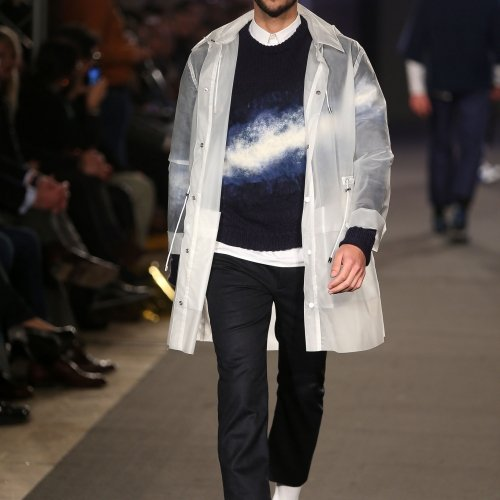 Male walking a catwalk, navy outfit, white overcoat and white flash across the front.