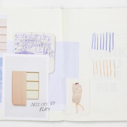 Open sketchbook, scribbles, photograph, pink and blue tones.
