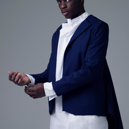 Male model wearing white shirt dress and navy tailored jacket with tails.