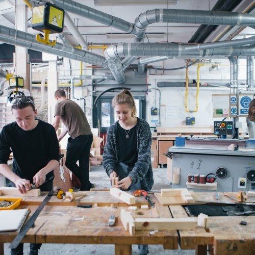 Female student and two male students in wood workshop