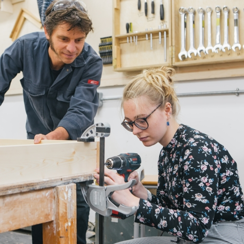 Female student and technician working in a workshop