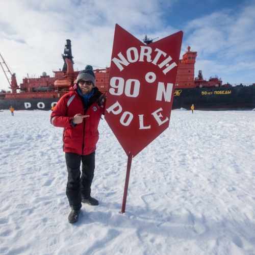 A man next to the North Pole sign with ship behind