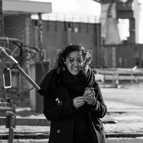 Black and white image of woman in a black coat smiling
